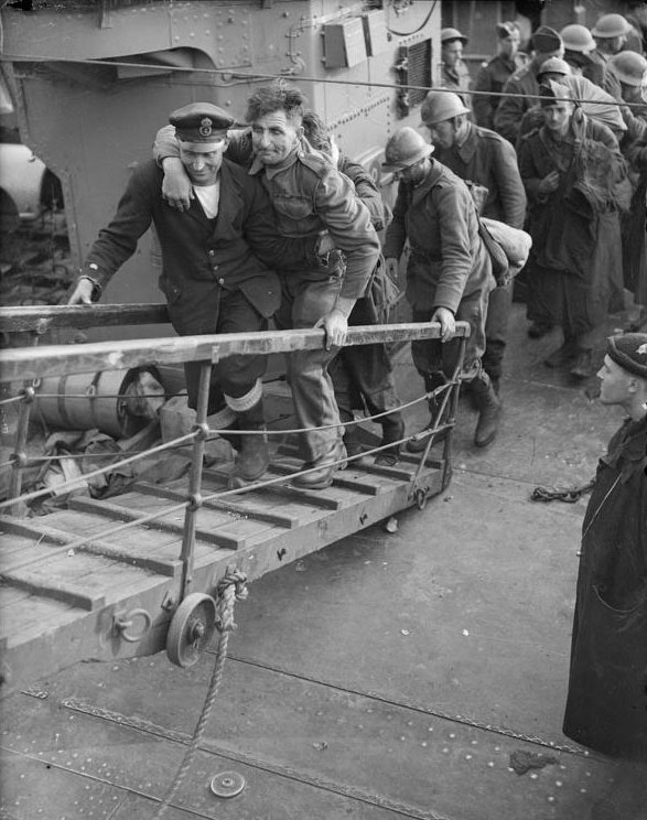 A merchant sailor assists a wounded british soldier up the gangplank from a destroyer, Dover, 31 May 1940