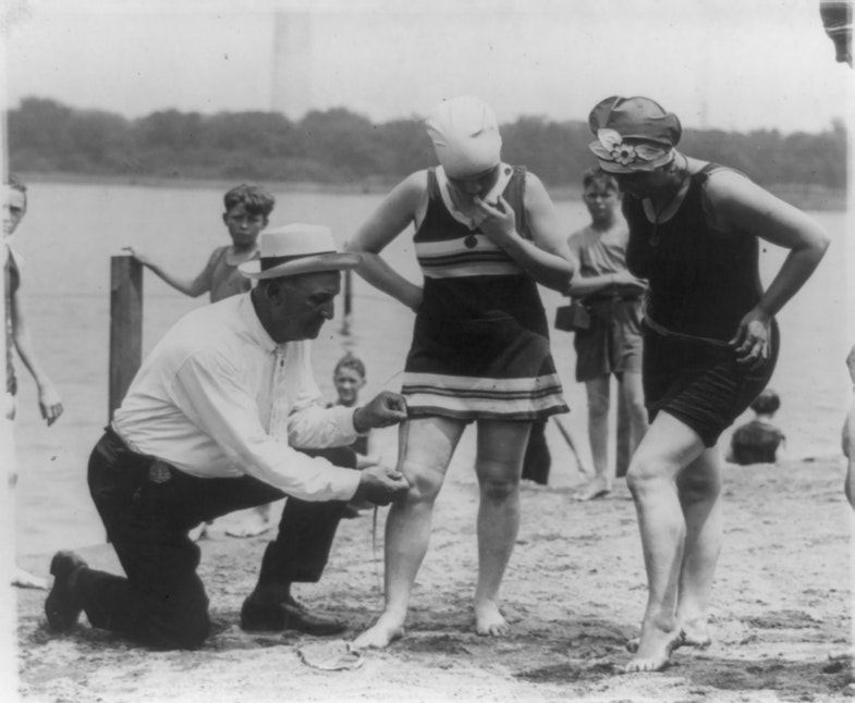Bill Norton the bathing beach policeman measuring distance between knee and bathing suit on woman, Washington, D.C