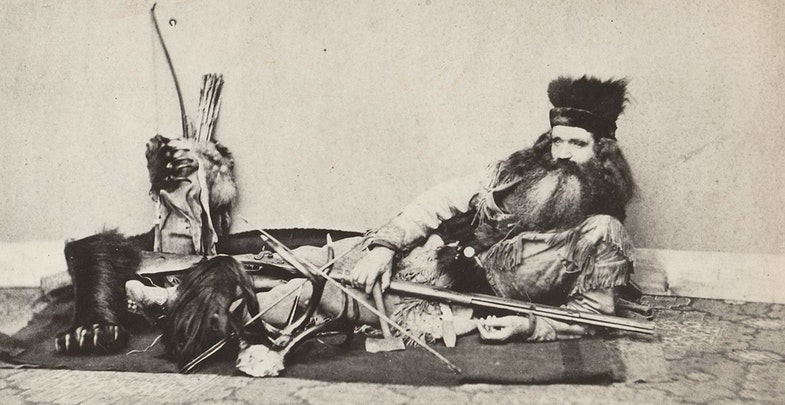 1864 photo of Californian Seth Kinman displaying an Indian scalp (front left). He collected