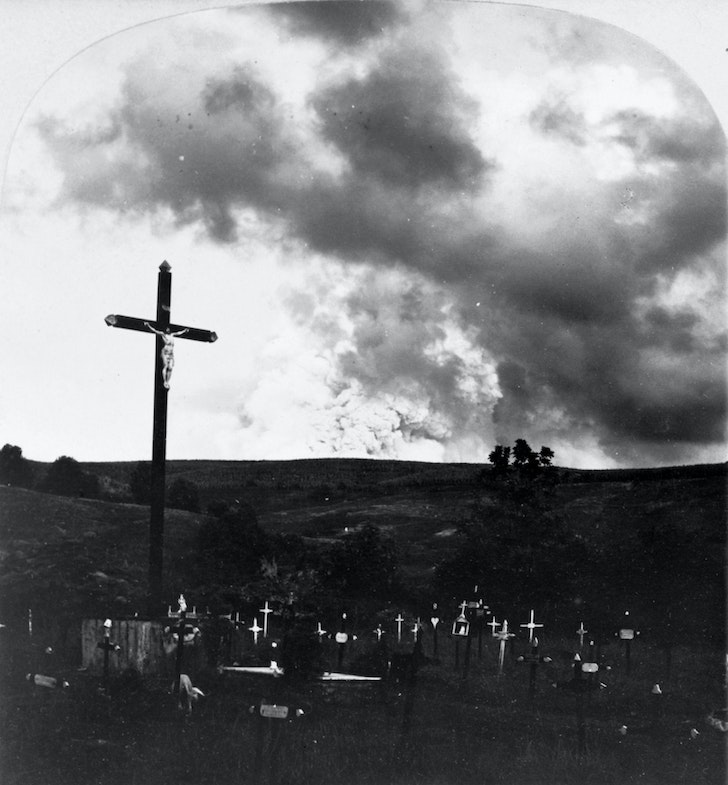 Graveyard in Martinique with large crucifix and crosses on graves; dense smoke rising from Mount Pelée eruption in background