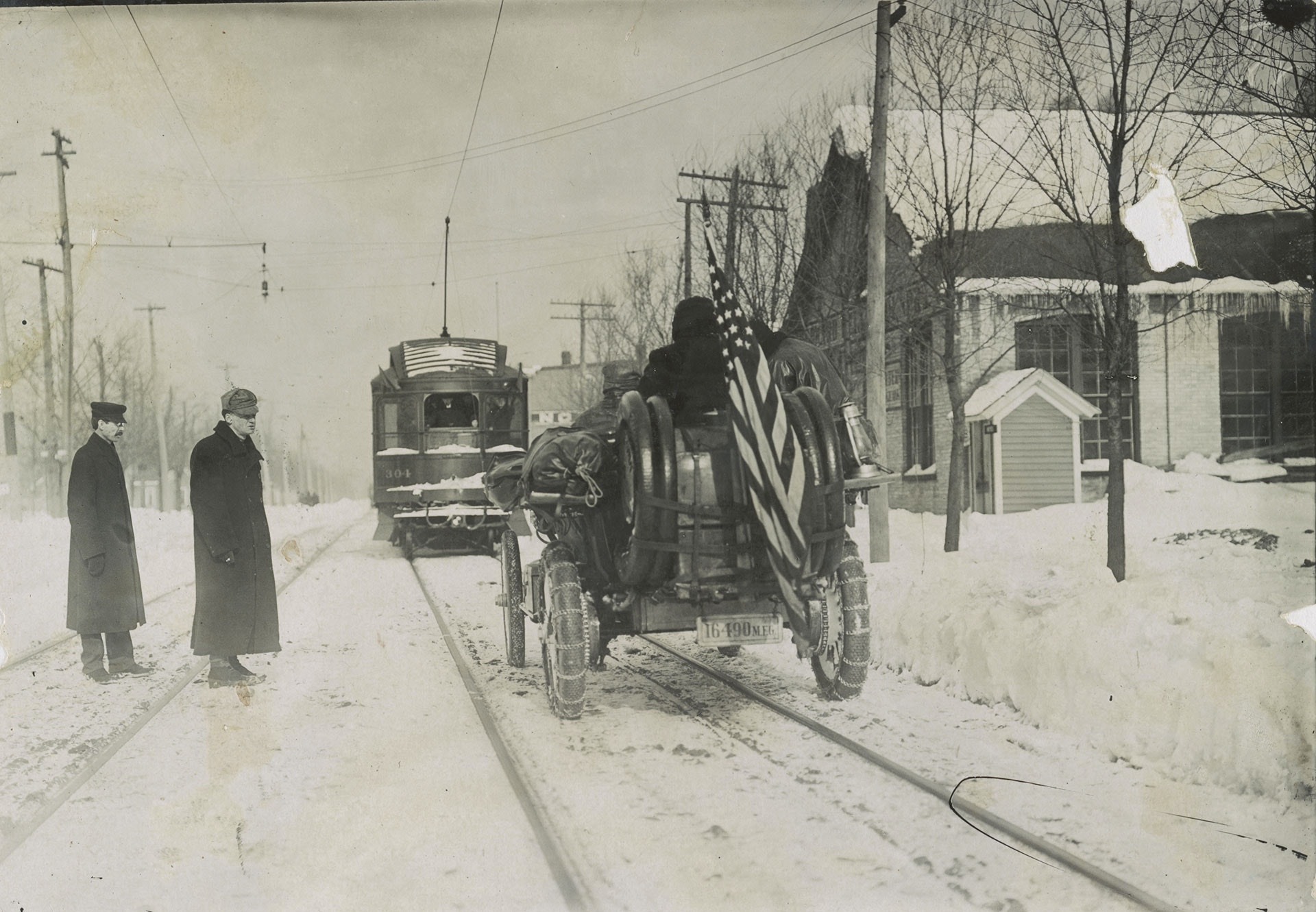 Thomas Flyer participating in New York-to-Paris automobile race driving behind a streetcar during the winter
