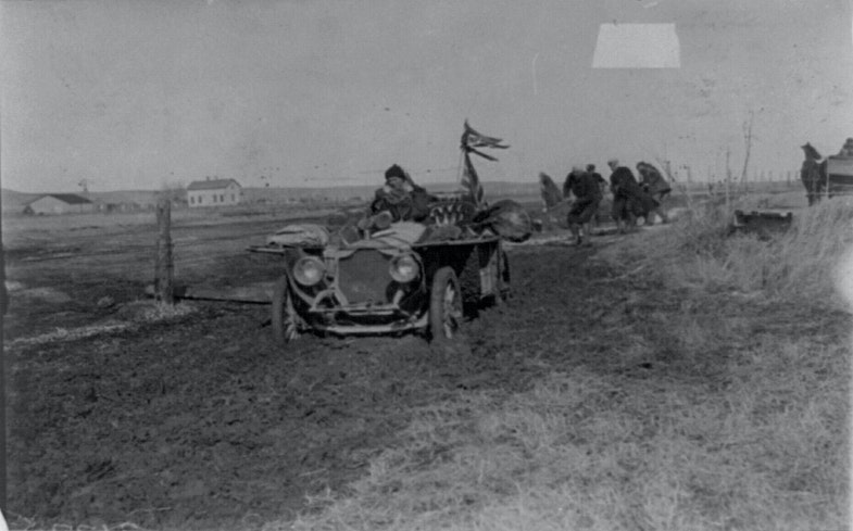 New York to Paris automobile race - five men trying to pull automobile out of mud