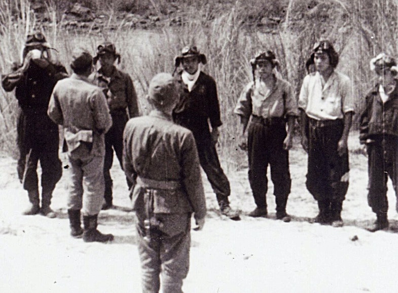 The photograph shows the men of the first actual Kamikaze unit to make an attack on a US ship. The men are being offerred a ceremonial toast of water as a farewell. Yukio Seki, the leader of the first kamikaze unit, is shown with a cup in his hands, and Vice Admiral Takijiro Onishi, who organized the first kamikaze unit, is in the middle of the photo facing the five men of the Shikishima Unit. The man offering the cup is likely Seki's officer, Asaiki Tamai