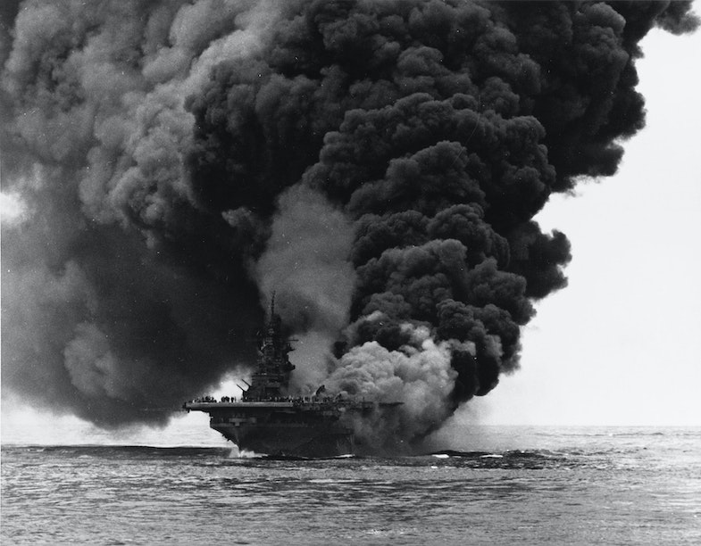 The U.S. Navy aircraft carrier USS Bunker Hill (CV-17) afire after being hit by two