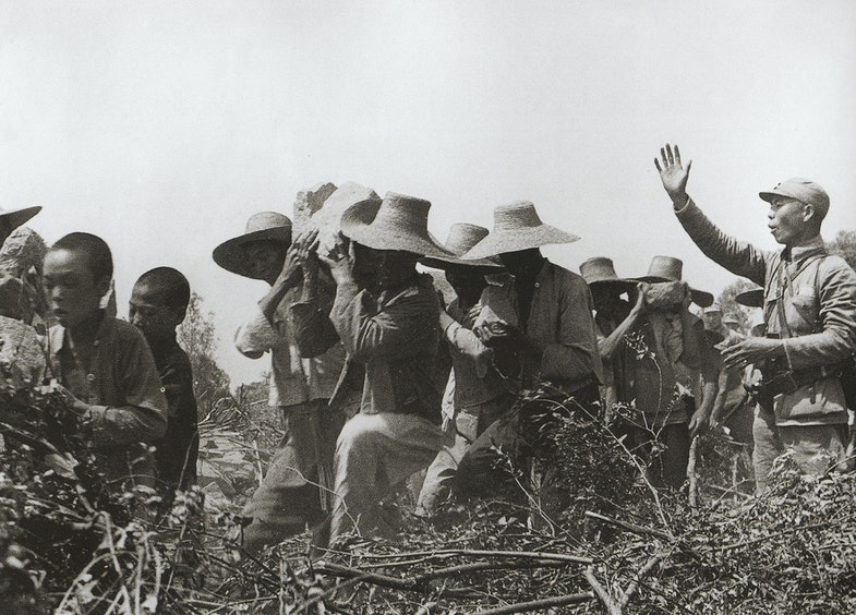 Nationalist soldier directing laborers working on dikes
