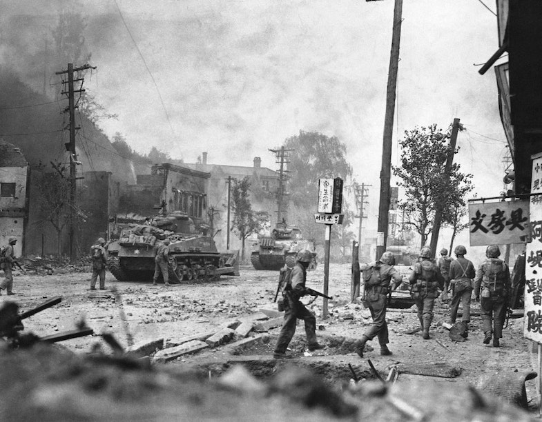Smoke rises over debris-littered streets as tanks lead U.N. forces in the recapture of Seoul, Korea, Sept. 28, 1950.