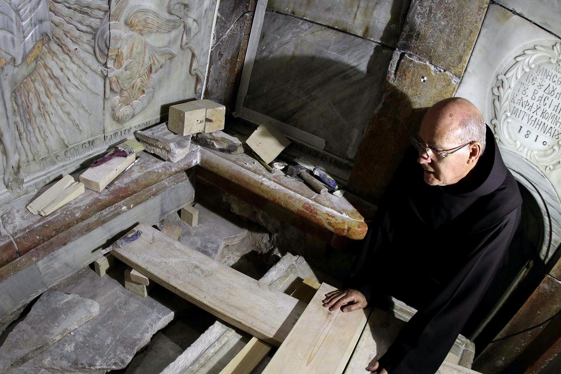 A Franciscan friar looks at the exposed the Tomb of Jesus