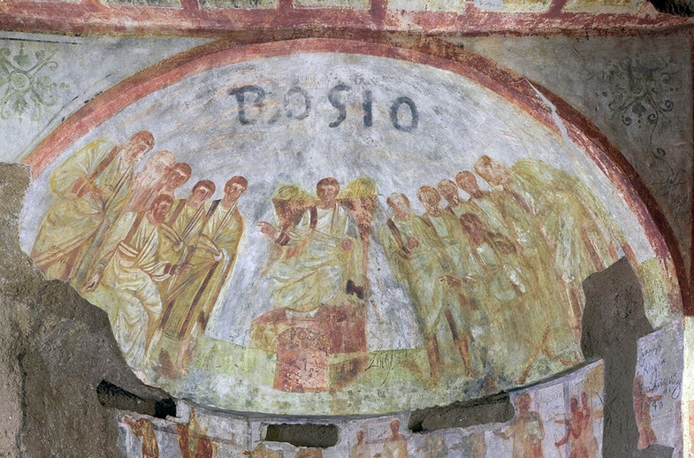 An image of Christ seated on a throne surrounded by his apostles can be seen in a burial chamber in the catacombs of St. Domitilla in Italy