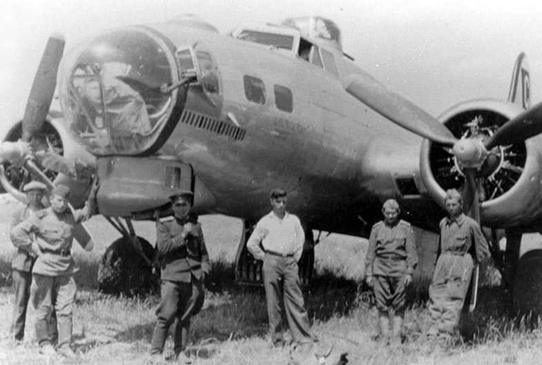 Badly damaged B-17 bomber and Russian soldiers in Poltava