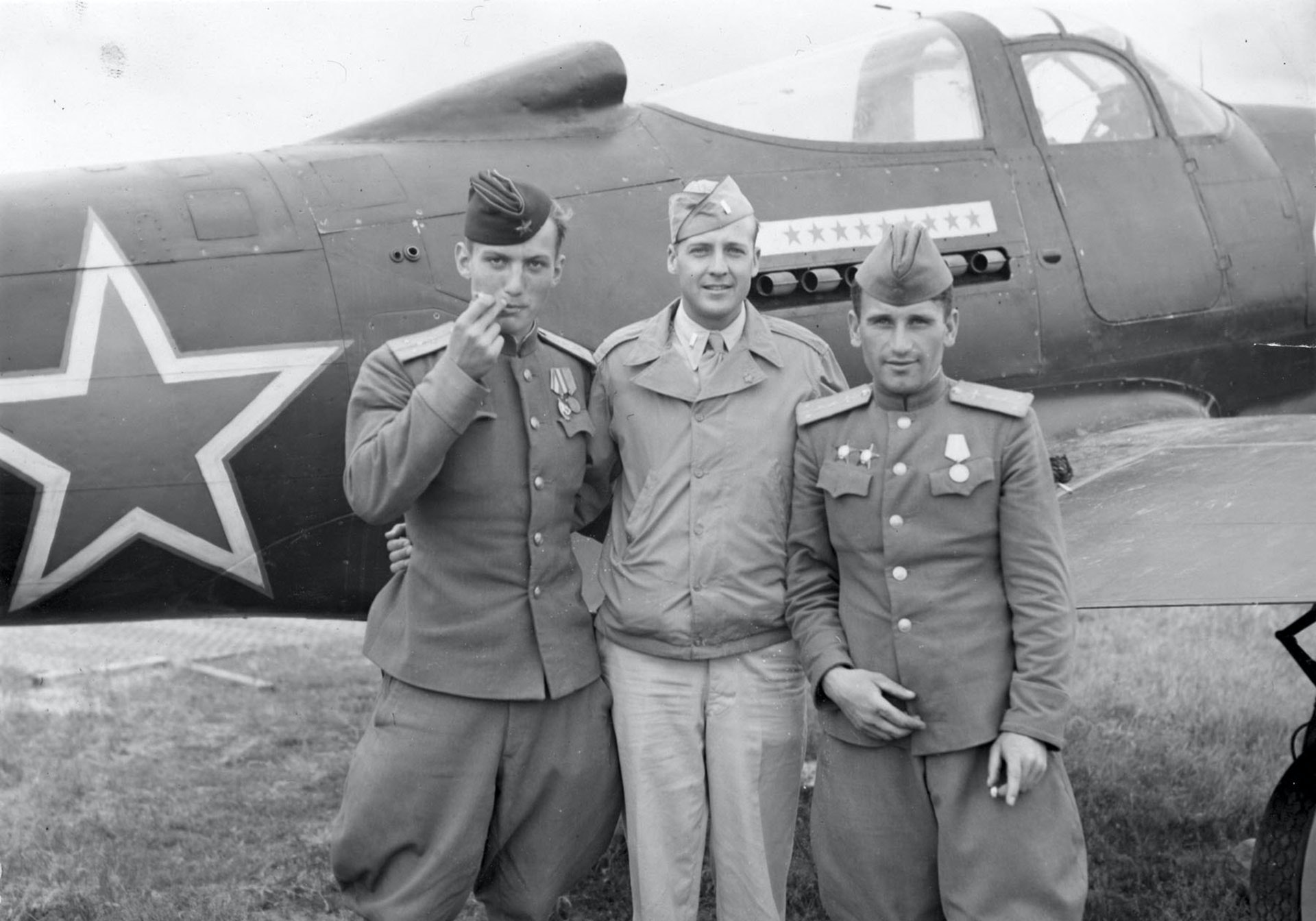 Andrea Hincerockur, a Russian pilot; Lt. Thompson Highfill of the 99th Bomb Ground; and Corzen Venzopkin, another Russia flier, pose behind a Soviet P-39