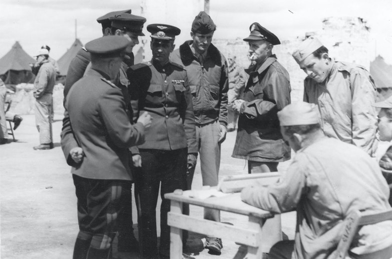 In the ruins of a hangar at Poltava, Gen. Porminov and Gen. Walsh listen to a pilot's report after the mission to Galati. The officer in the center is Capt. Henry Ware, interpreter from Gen. Deane's staff.