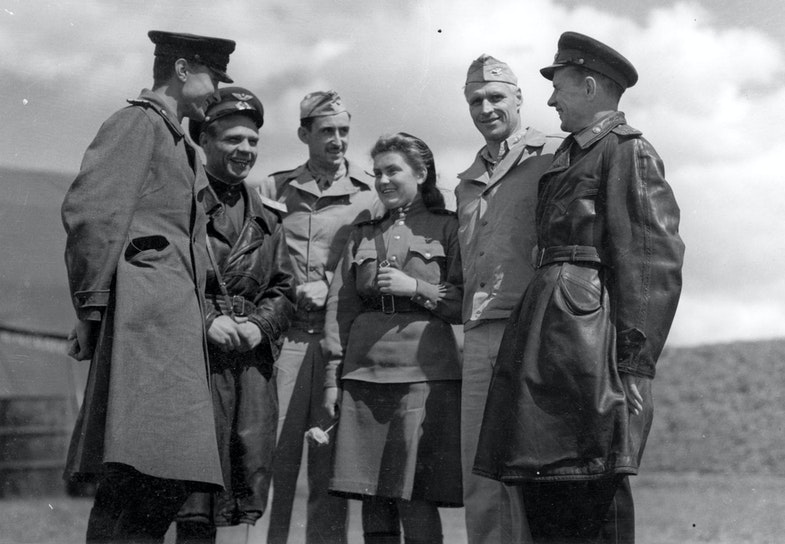 Russian officers chat with Col. Barton, commanding officer of the 483rd Bomb Group, and Col. Rice of the 2nd Bomb Group at Mirgorod. The girl in the center is an interpreter
