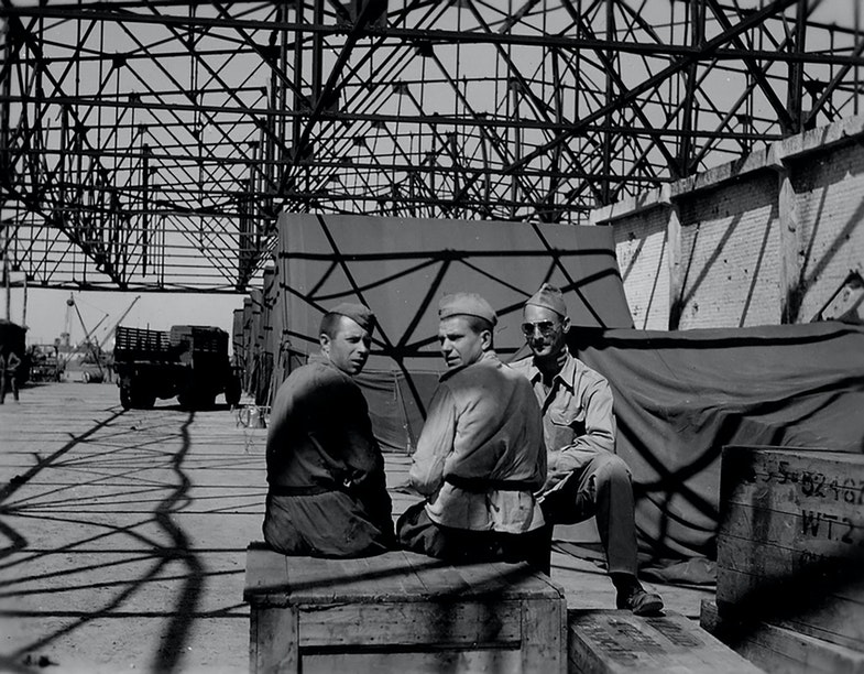 Soviet soldiers and an American soldier in the warehouse of the airfield
