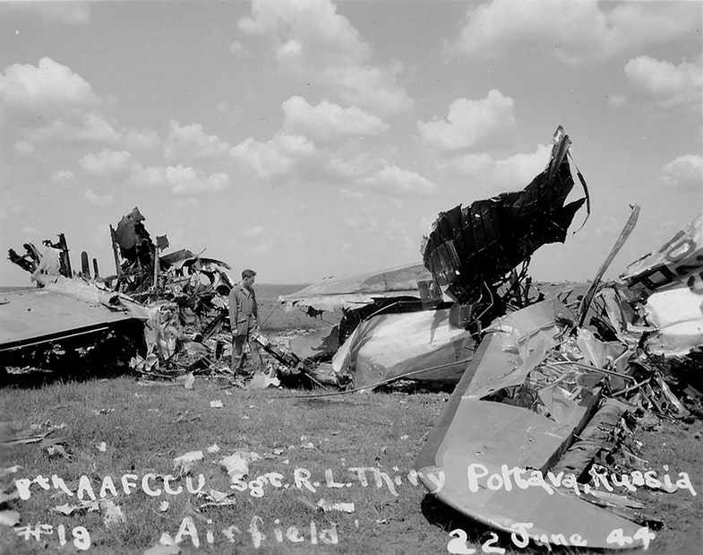 Technician among the wreckage of the B-17 bomber destroyed by the German bombardment