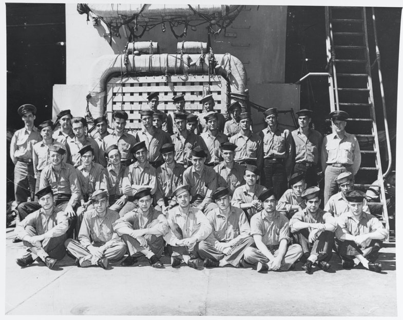 Members of the ship's crew pose in the well deck, during World War II. Photograph was taken prior to her final overhaul (completed in July 1945), as life rafts are of a different pattern than carried after that overhaul. Photograph was received by the Naval Photographic Science Laboratory on 24 August 1945