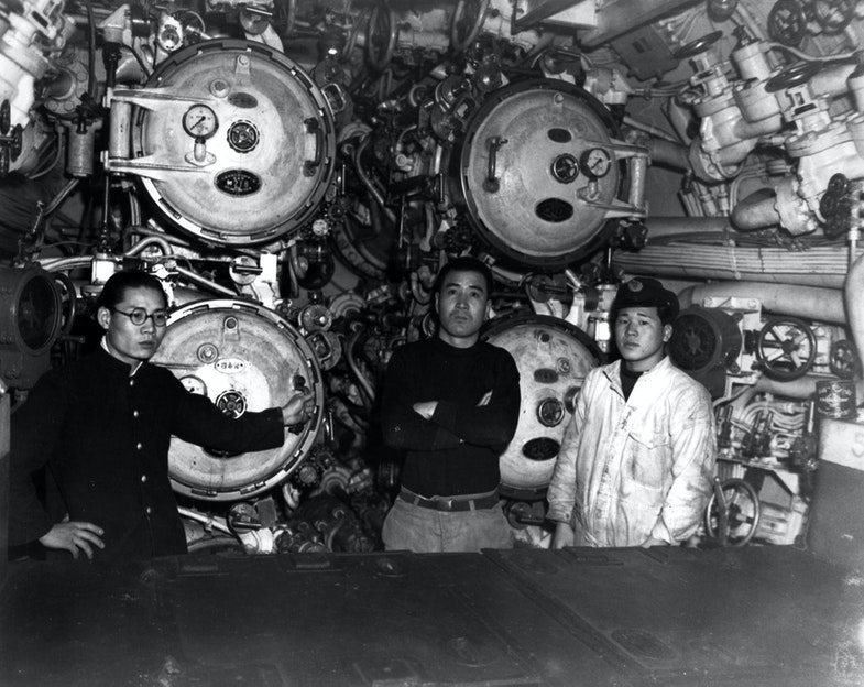 View in the forward torpedo room, showing 21-inch torpedo tubes and three crew members. Taken at Sasebo, Japan, 28 January 1946. This submarine torpedoed and sank USS Indianapolis (CA-35) on 30 July 1945
