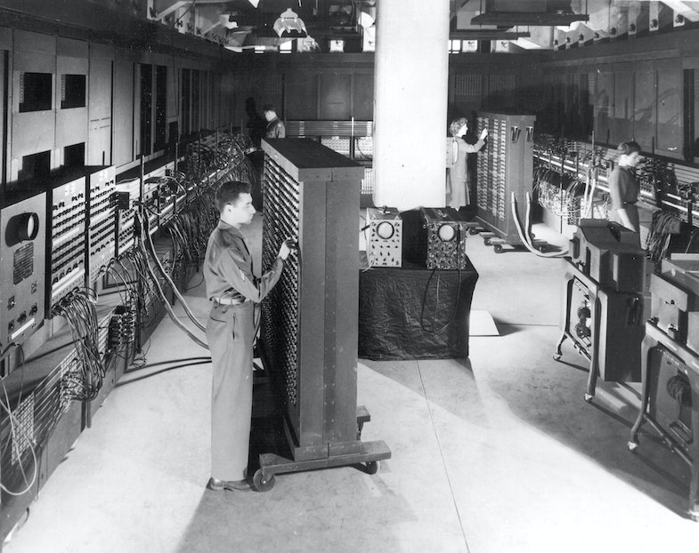 Cpl. Irwin Goldstein (foreground) sets the switches on one of the ENIAC's function tables at the Moore School of Electrical Engineering.