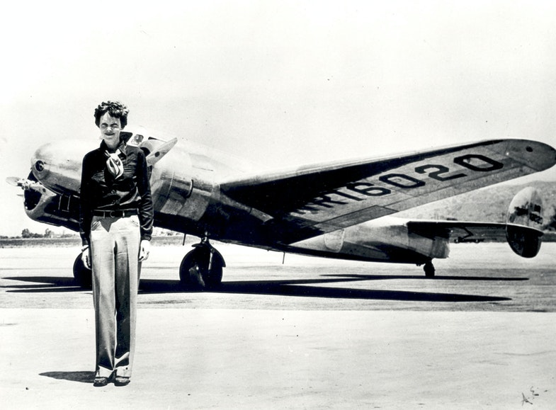 Amelia Earhart standing in front of the Lockheed Electra