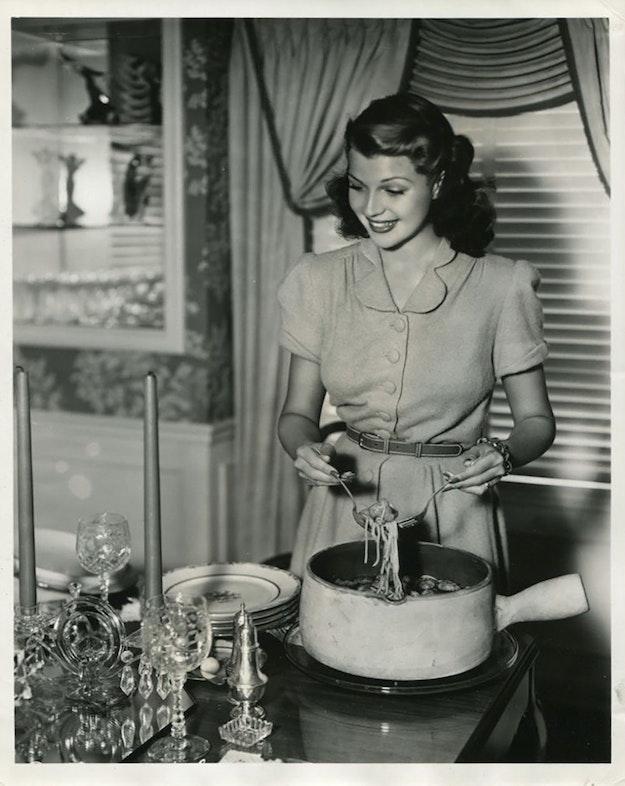 RITA HAYWORTH SERVES UP SPAGHETTI - 1941