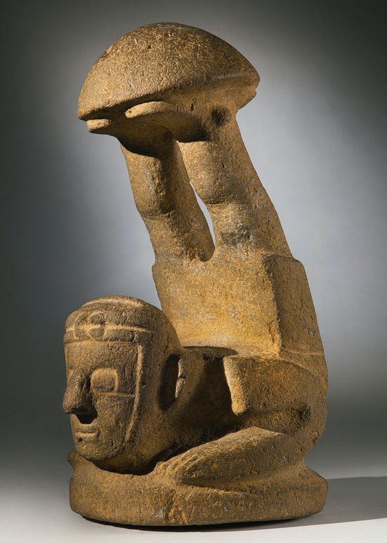 the ''mushroom' stone in the form of the acrobat figure, with legs sharply thrown up and supporting the domed cap on both feet, with squared torso and arms, large squared eyes and wearing a turban knotted on the forehead; in gray-tan basalt