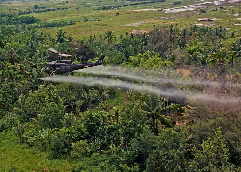 Vietnam. Defoliation Mission. A UH-1D helicopter from the 336th Aviation Company sprays a defoliation agent on agricultural land in the Mekong delta