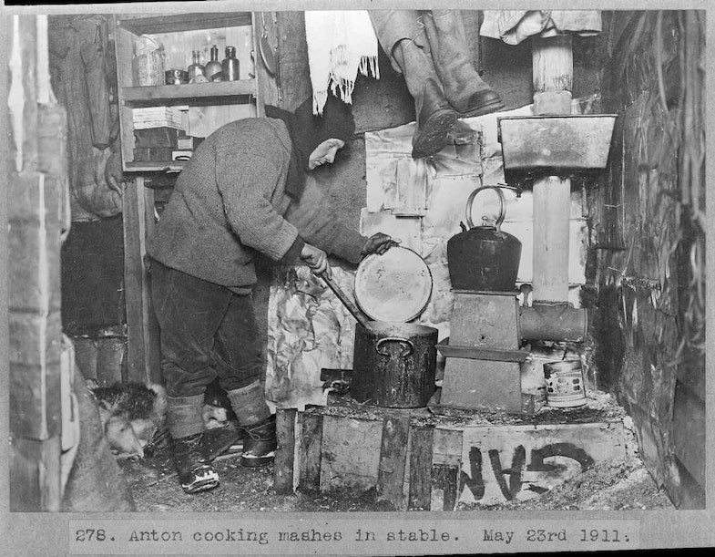Anton Omelchenko cooking mash in the stable during the British Antarctic Expedition of 1911-1913