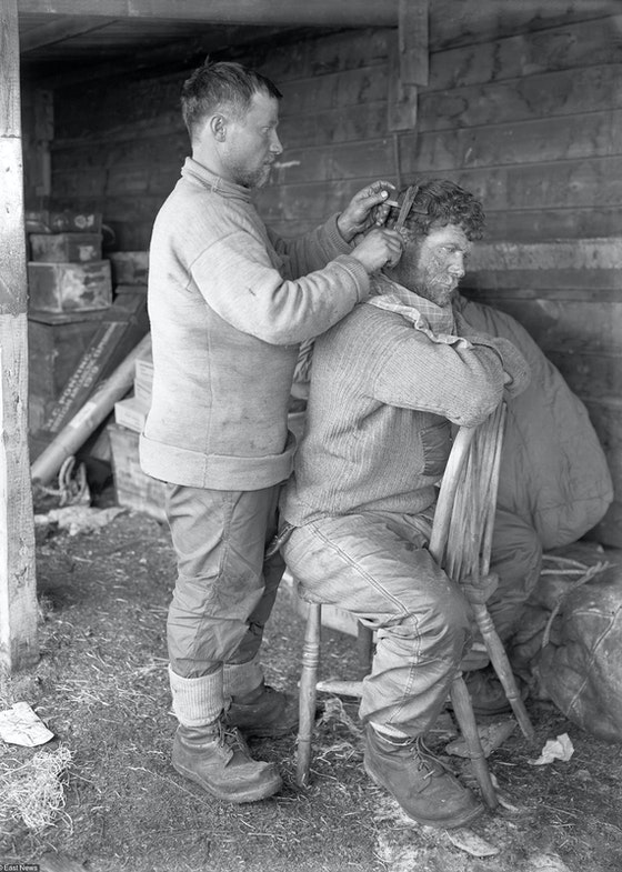 Russian groom Anton Omelchenko (left, 1883-1932) cutting the hair of Irish explorer and British Royal Navy petty officer Patrick Keohane (right, 1879-1950) at the Cape Evans base camp in January 1912 during the British Antarctic Expedition (1910-1913). Also known as the Terra Nova Expedition