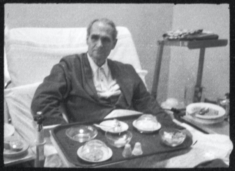 Clandestine photographs of Rudolf Hess sitting in his hospital bed with his tray of food in the Spandau Prison