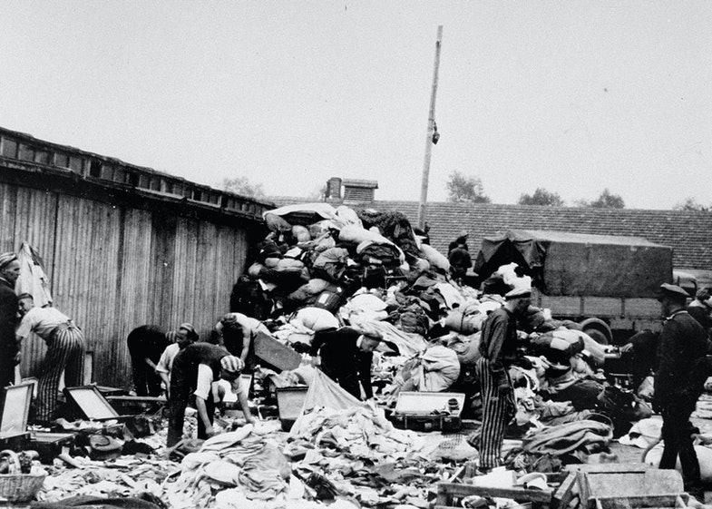 Prisoners in the Aufräumungskommando (order commandos) unload and sort the confiscated property of a transport of Jews from Subcarpathian Rus at a warehouse in Auschwitz-Birkenau