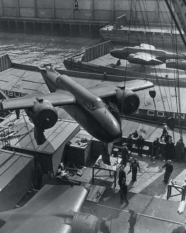 American twin-engine bombers, provided by lend-lease, are shown being hoisted aboard ship in an unnamed American port.